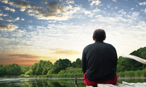 Man sitting on pier at lake